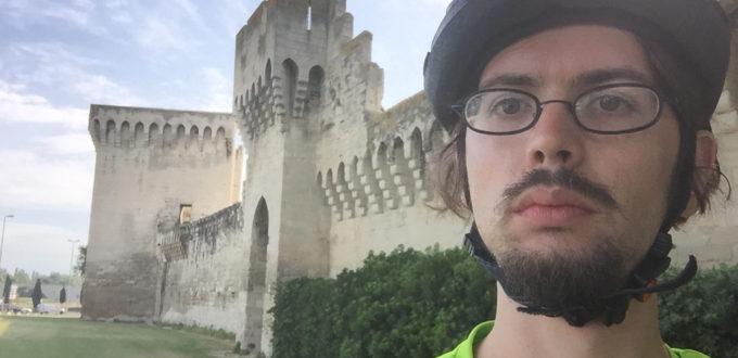 Mit Fahrradhelm vor der Mauer in Avignon