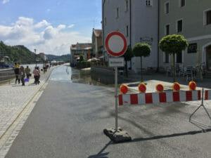 Hochwasser Dreiflüssestadt Passau am Donauradweg mit Schild und Wasser