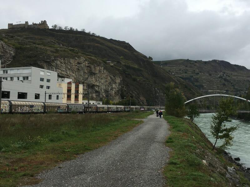 Sion, zu deutsch Sitten mit dem Schloss Tourbillon links oben auf einem Schotterweg, auf der rechten Seite befindet sich die Rhone.