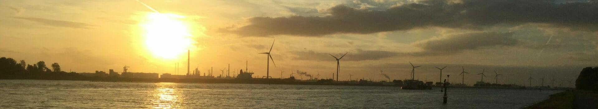 Hafen von Rotterdam, ganz viele Windkraftanlagen von weitem, dazu eine rote, schöne Sonne - Niederlande.